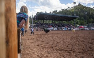 Woman watches as bull rider tries to hang on