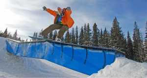 A snowboarder catches some air at terry peak ski area