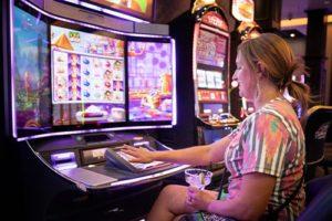 Lady playing slots in Cadillac Jacks
