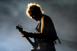 Man playing electric guitar on foggy stage
